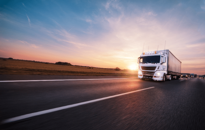truck driving along the road at sunset