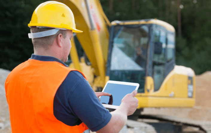 construction worker using tablet with machinery in background