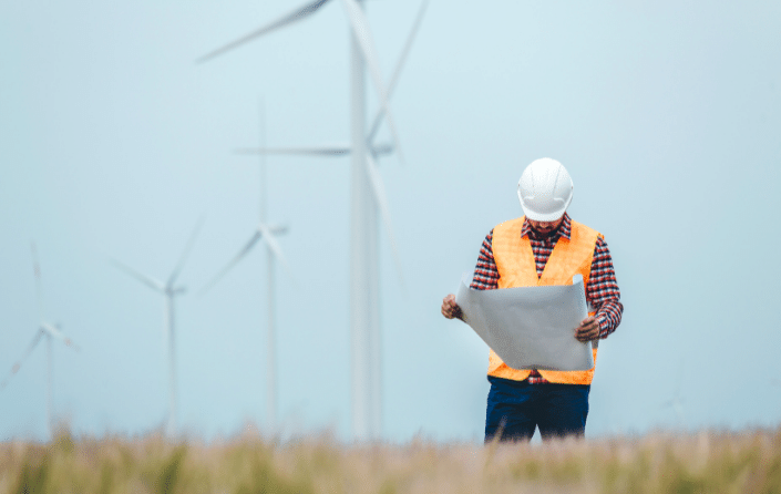 worker in high vis jacket reading paperwork, with wind turbines in background